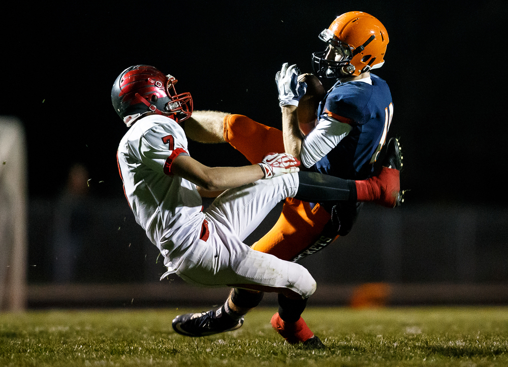 Rochester's Tyler Mazzini (18) comes down with a pass against Mt. Zion's Peyten Chappel (7) in the first half during the first round of the Class 4A playoffs at Rocket Booster Field, Saturday, Nov. 1, 2014, in Rochester, Ill. Justin L. Fowler/The State Journal-Register