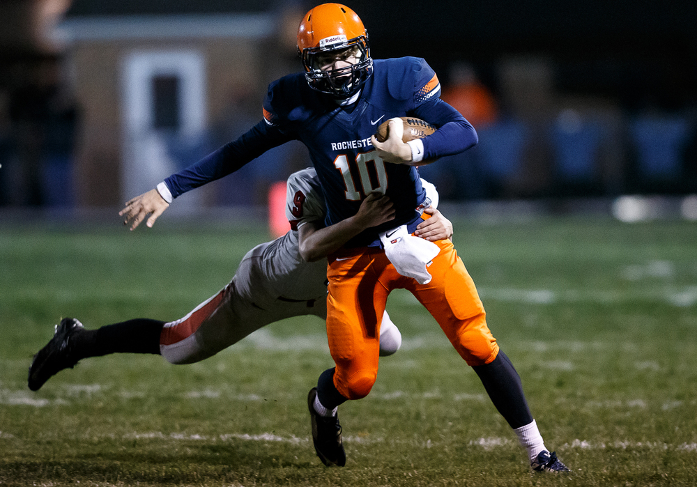 Rochester's Danny Zeigler (10) is brought down by Mt. Zion's Justin May (9) after scrambling from the pocket in the second half during the first round of the Class 4A playoffs at Rocket Booster Field, Saturday, Nov. 1, 2014, in Rochester, Ill.   Justin L. Fowler/The State Journal-Register