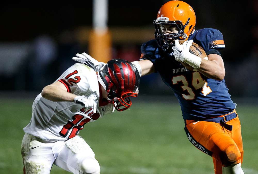 Rochester's Evan Sembell (34) puts a stiff arm on Mt. Zion's Austin Thacker (12) as he tries to bring him down on a rush in the first half during the first round of the Class 4A playoffs at Rocket Booster Field, Saturday, Nov. 1, 2014, in Rochester, Ill. Justin L. Fowler/The State Journal-Register