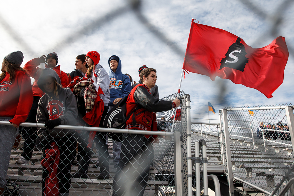 Springfield student Joe Locher brings in the school flag as the student section fills in to cheer on their team against West Chicago Wheaton Academy during the IHSA Class 2A Soccer State Final Tournament semifinals at Hoffman Estates High School, Friday, Nov. 7, 2014, in Hoffman Estates, Ill. Justin L. Fowler/The State Journal-Register