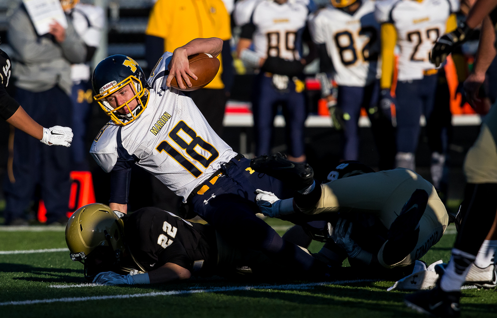 Marion quarterback Izak Baker (18) is brought down by Sacred Heart-Griffin's Sean Mason (86) on a rush in the second half during the second round of the Class 5A playoffs at the SHG Sports Complex, Saturday, Nov. 8, 2014, in Springfield, Ill. Justin L. Fowler/The State Journal-Register