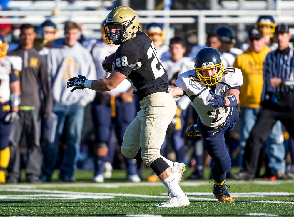Sacred Heart-Griffin's Sam Sergent (28) breaks a tackle from Marion's Matt McAuliffe (21) on a rush in the first half during the second round of the Class 5A playoffs at the SHG Sports Complex, Saturday, Nov. 8, 2014, in Springfield, Ill. Justin L. Fowler/The State Journal-Register