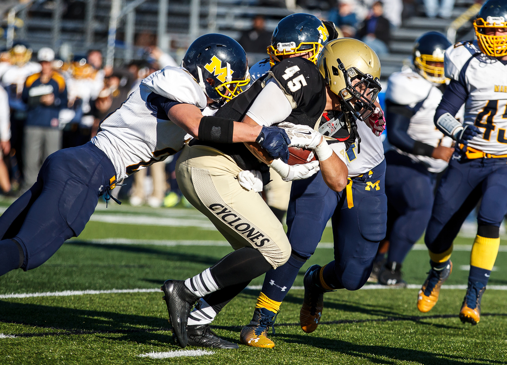 Sacred Heart-Griffin's Anthony DiNello (45) protects the ball as he is brought down by Marion's Matt McAuliffe (21) in the first half during the second round of the Class 5A playoffs at the SHG Sports Complex, Saturday, Nov. 8, 2014, in Springfield, Ill. Justin L. Fowler/The State Journal-Register