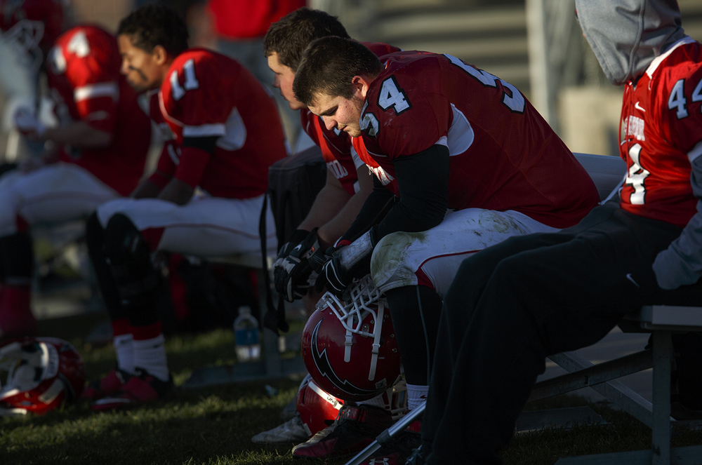 Chatham Glenwood's Andrew Banaitis sits with his teammates on the bench after the Titans fell behind 41-0 to Peoria Notre Dame in the fourth quarter of the Class 6A high school football playoffs at Chatham Glenwood Saturday, Nov. 8, 2014. Ted Schurter/The State Journal-Register
