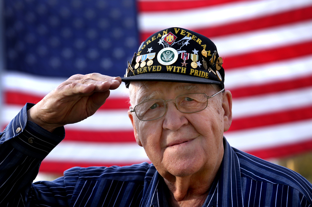 "Mason City resident and Korean War veteran Dean Lynn salutes Wednesday while wearing his ""heavy metal"" cap adorned with miniature versions of some of the medals he received during the Korean War. David Spencer/The State Journal-Register"