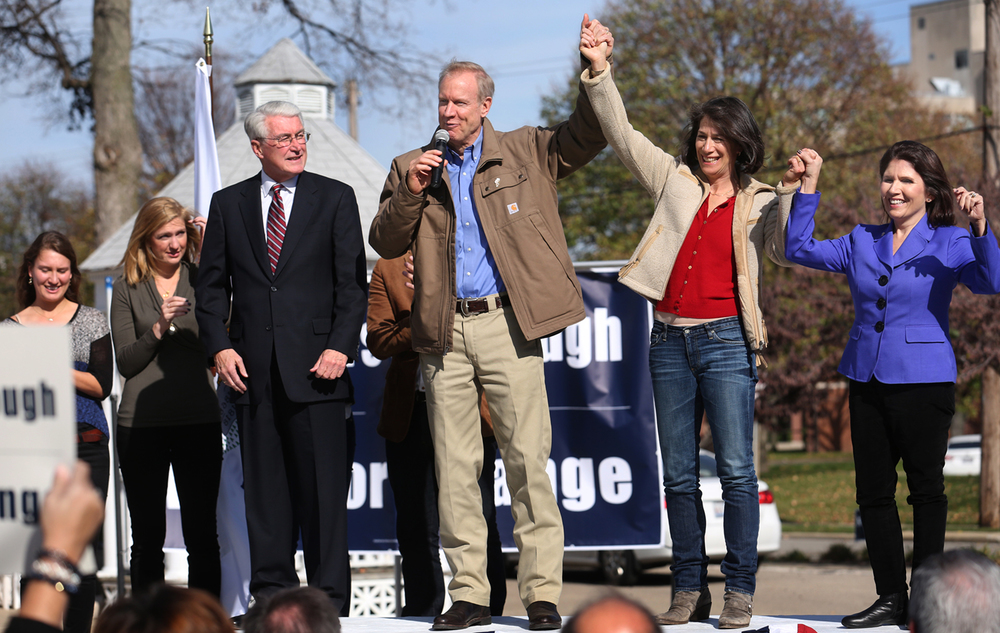 With former Gov. Jim Edgar looking on at left, Republican challenger for governor Bruce Rauner holds up the hand of his wife Diana Rauner, who holds up the hand of lieutenant governor candidate Evelyn Sanguinetti during a rally outside of the Pasfield House in Springfield on Monday, Nov. 3, 2014. David Spencer/The State Journal-Register