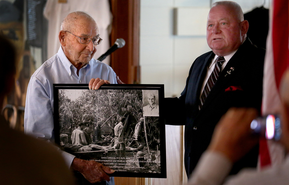 James LaRocca, 96, of Springfield, a Second Lieutenant in the U.S. Army who served as a Litter Officer in the Asian-Pacific Theatre during World War II and currently the oldest active member of Springfield Elks Lodge No. 158 when he joined in 1949, was honored as the Elks Veteran of the Year for the lodge during a Veterans Day luncheon on Friday, Nov. 7, 2014. Along with a bust of Abraham Lincoln, lodge Leading Knight Bobby Edwards presented LaRocca with a framed photograph featuring his service photo and enlarged photo of U.S. soldiers being evacuated on stretchers during WWII.  David Spencer/The State Journal-Register