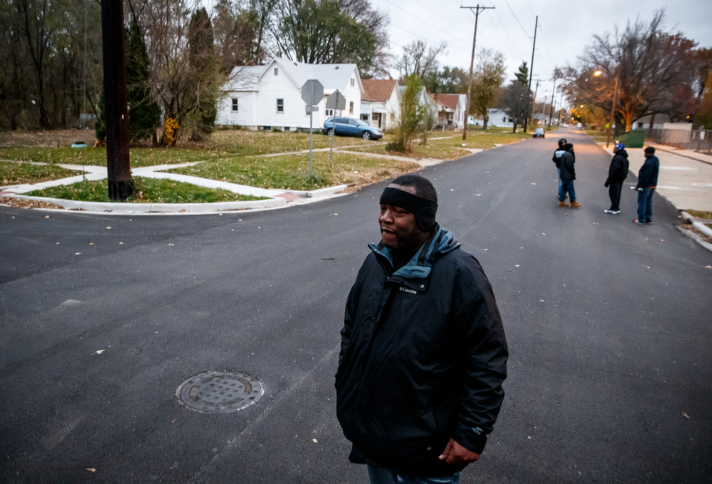 Curtis Bounds, an outreach worker with the Springfield Urban League, looks back to invite someone that wanted to join the march from their porch during the Stop the Violence Walk for Peace & Prayer Vigil in response to the murder of Kirk Hardy, Tuesday, Nov. 11, 2014, in Springfield, Ill. Justin L. Fowler/The State Journal-Register
