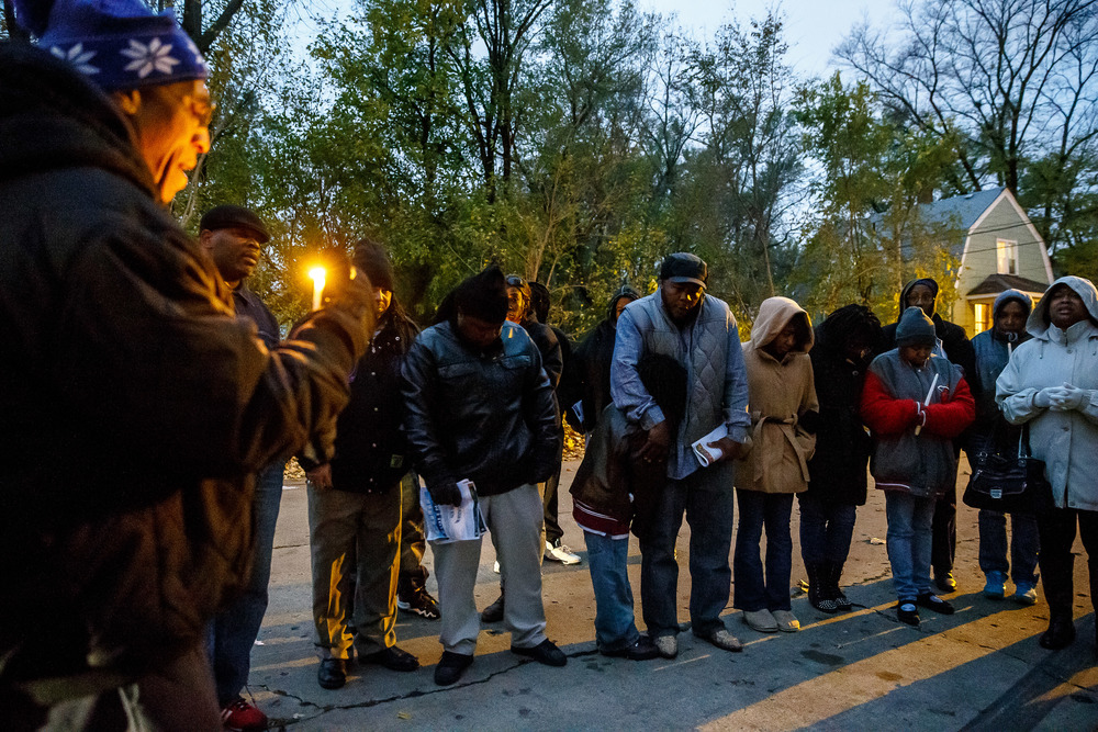 Pastor Donald Mayes, left, leads a prayer for those gathered at the site of the murder of Kirk Hardy after the Stop the Violence Walk for Peace & Prayer Vigil on Cass Street between 13th and 14th, Tuesday, Nov. 11, 2014, in Springfield, Ill. Justin L. Fowler/The State Journal-Register