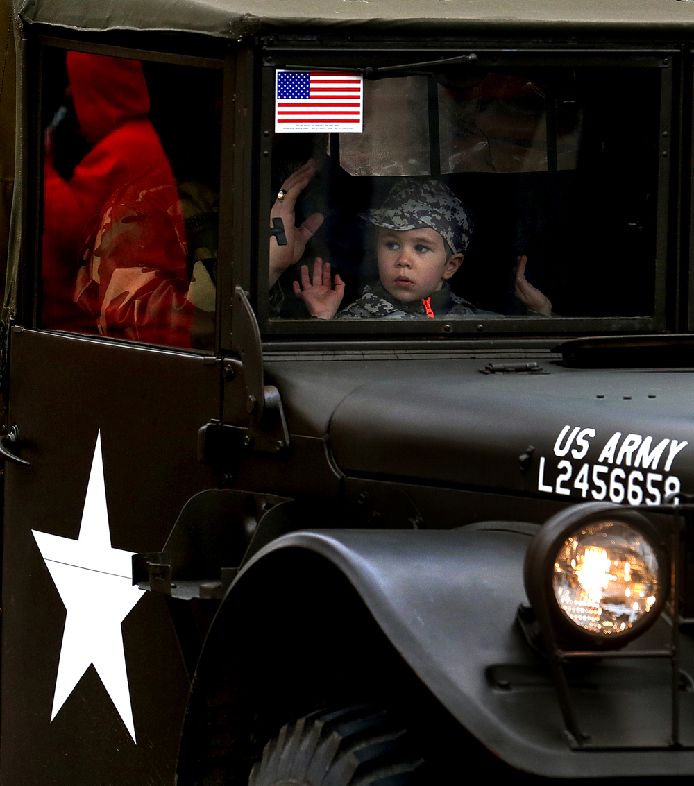 A young boy rides in the cab of an Army truck-part of a convoy of vehicles from the Illinois State Military Museum who took part in the parade. Springfield's annual Veterans Day parade took place on Capitol Ave. on Tuesday morning, Nov. 11, 2014. David Spencer/The State Journal-Register