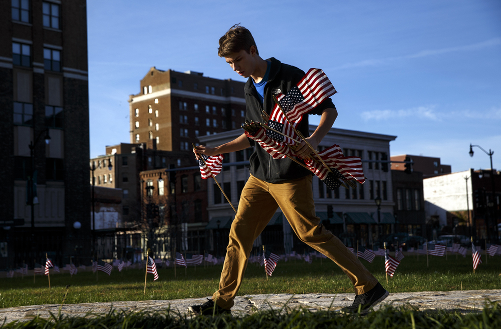 "Derrick Duzan carries an armload of flags as he and about a dozen volunteers place some of the 3,512 of them on the lawn of the Old State Capitol for the ""Hallowed Ground"" display Sunday, Nov. 10, 2014.  The number of flags represents the number of Union soldiers buried at Gettysburg, the bloodiest battle of the Civil War. Ted Schurter/The State Journal-Register"