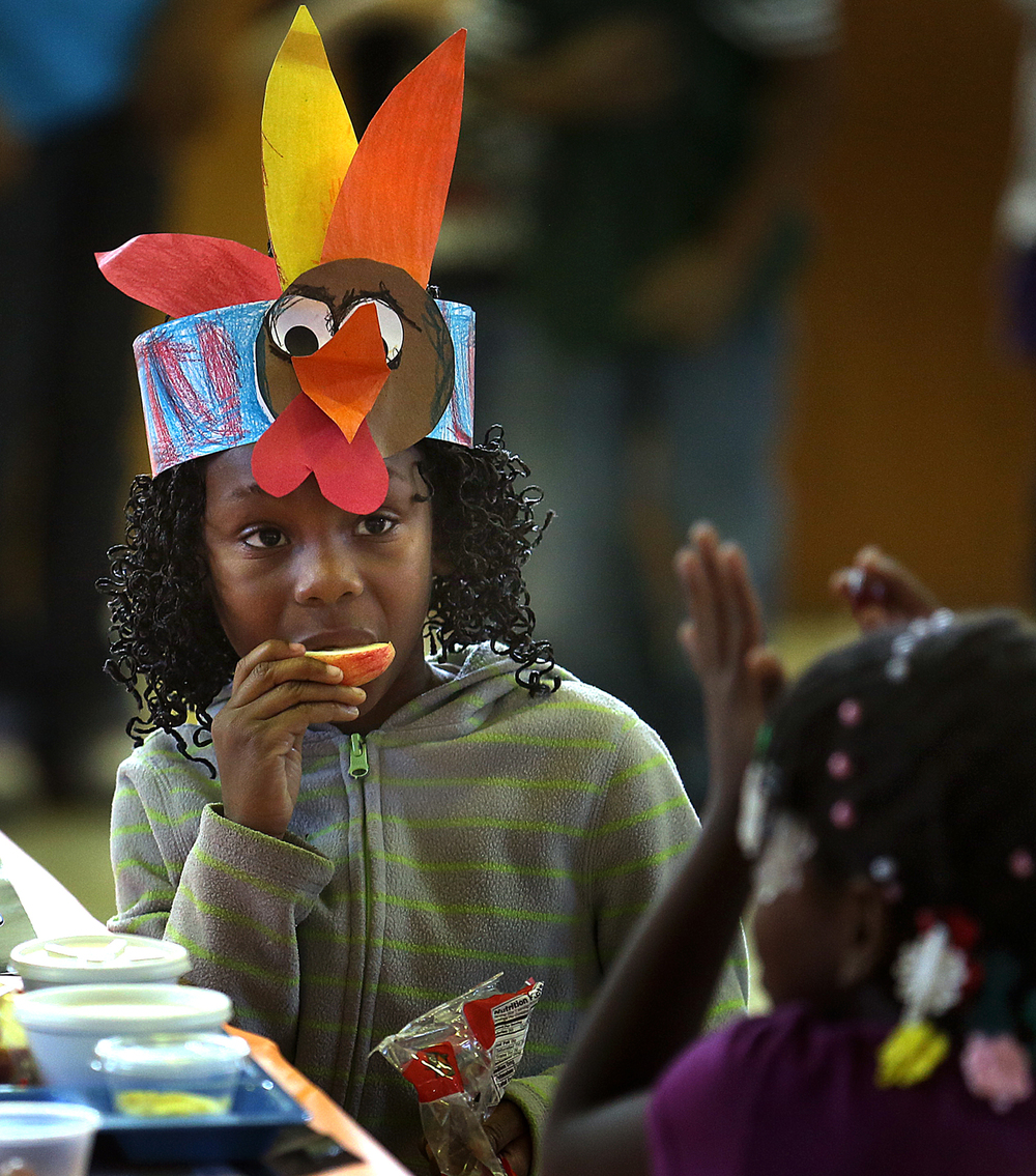 "First grade student Kori Moore enjoys lunch along with seatmate Carlaysia Kirkwood at Lee Elementary School's 15th annual Thanksgiving meal for students and family Thursday, Nov. 20, 2014. Kindergarten, first grade and K-2nd special needs classes and their families are invited. ""The diverse population of students will come together and share the Lee Lion spirit as they reflect upon how thankful they are to care for one another throughout the year,"" said Lee School principal Nathan Kochanowski. David Spencer/The State Journal-Register"