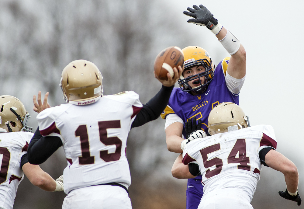 Williamsville's Mitch Whitley pressures Mt. Carmel's Pete Smith as he passes the balll during the Class 3A high school football playoffs in Williamsville Saturday, Nov. 22, 2014. Ted Schurter/The State Journal-Register