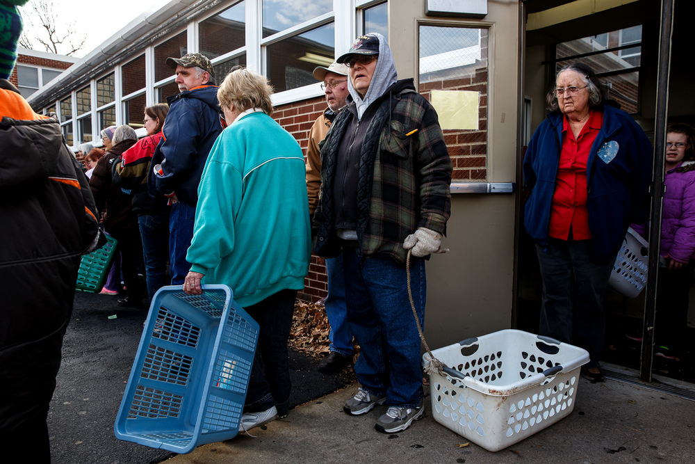 "Doreen Hilbert, of Taylorville, Ill., an Army Veteran, waits in line with her laundry basket to fill up with food from a mobile food pantry by the Central Illinois Foodbank at Taylorville High School, Saturday, Nov. 22, 2014, in Taylorville, Ill. ""It'll last me a little bit,"" said Halbert of the food basket. ""To get off of public aid and get a full time job...so I can survive. Thats my wish for Thanksgiving."" Justin L. Fowler/The State Journal-Register"