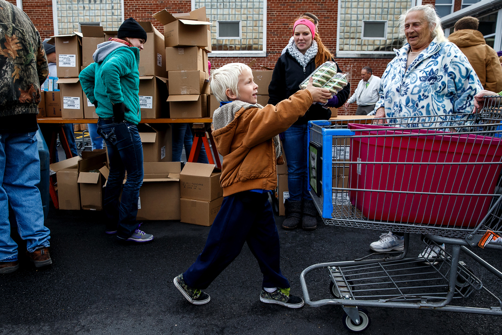 Preston Beitel, 6, loads a batch of cookies into a cart as he helps get food for his family along with this grandmother, Billie Durbin, at a mobile food pantry by the Central Illinois Foodbank at Taylorville High School, Saturday, Nov. 22, 2014, in Taylorville, Ill. Families were about to get a full box of food including a ham and canned goods along with the cookies. Justin L. Fowler/The State Journal-Register