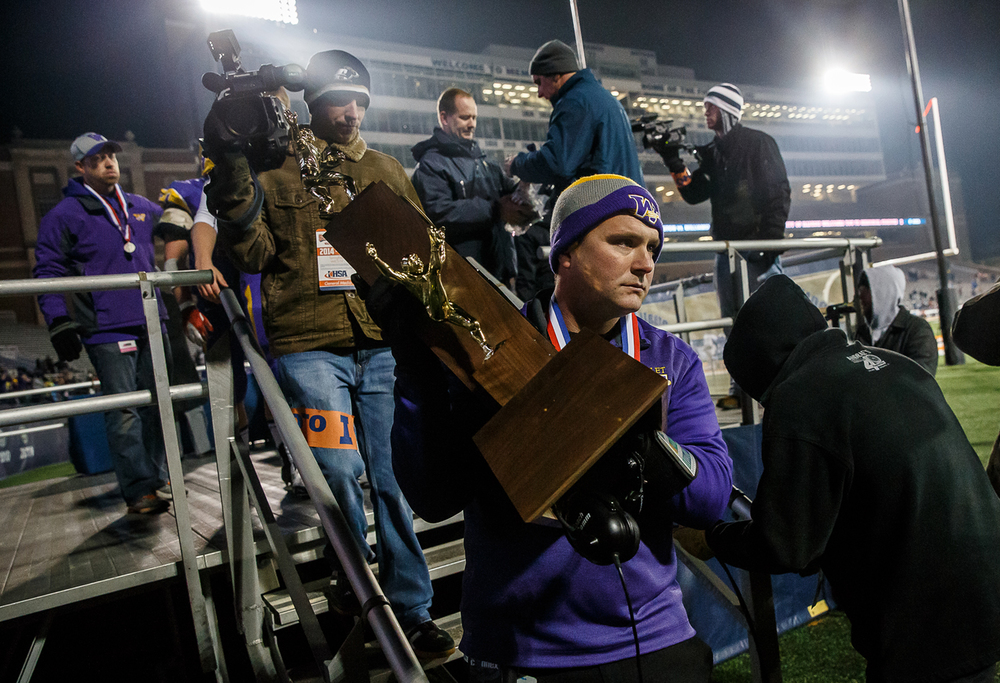 Williamsville head football coach Aaron Kunz carries down the second place trophy after the Bullets were defeated 20-17 by Wilmington in the IHSA Class 3A state championship game at Memorial Stadium, Friday, Nov. 28, 2014, in Champaign, Ill. Justin L. Fowler/The State Journal-Register