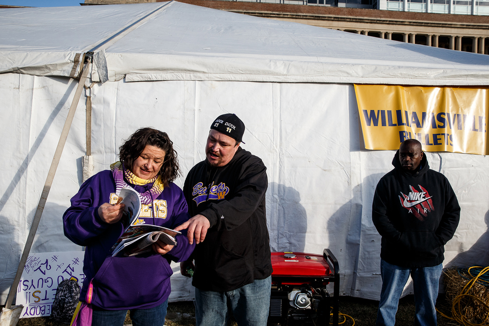 Daniel Rich, of Anchorage, Alaska, center, points out a picture of his nephews Williamsville's D'ante' Cox (11) and Avante' Cox (21) as he looks through the program with their mother Jo Lacy outside the teams tent prior to WIliamsville taking on Wilmington in the IHSA Class 3A state championship game at Memorial Stadium, Friday, Nov. 28, 2014, in Champaign, Ill. Justin L. Fowler/The State Journal-Register