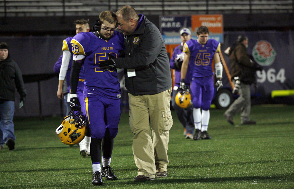 Williamsville's Grant Luckhart is consoled as he walks off the field after the Bullets lost to Wilmington during the Class 3A football championship game at Memorial Stadium Friday, Nov. 28, 2014. Ted Schurter/The State Journal-Register
