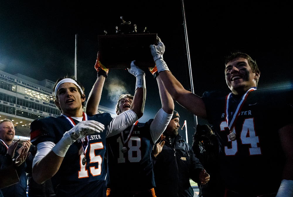 Rochester's Jeremy Bivens (15) Tyler Mazzini (18) and Evan Sembell (34) celebrate with the trophy after defeating Chicago Phillips in the IHSA Class 4A state championship game at Memorial Stadium, Friday, Nov. 28, 2014, in Champaign, Ill. Justin L. Fowler/The State Journal-Register