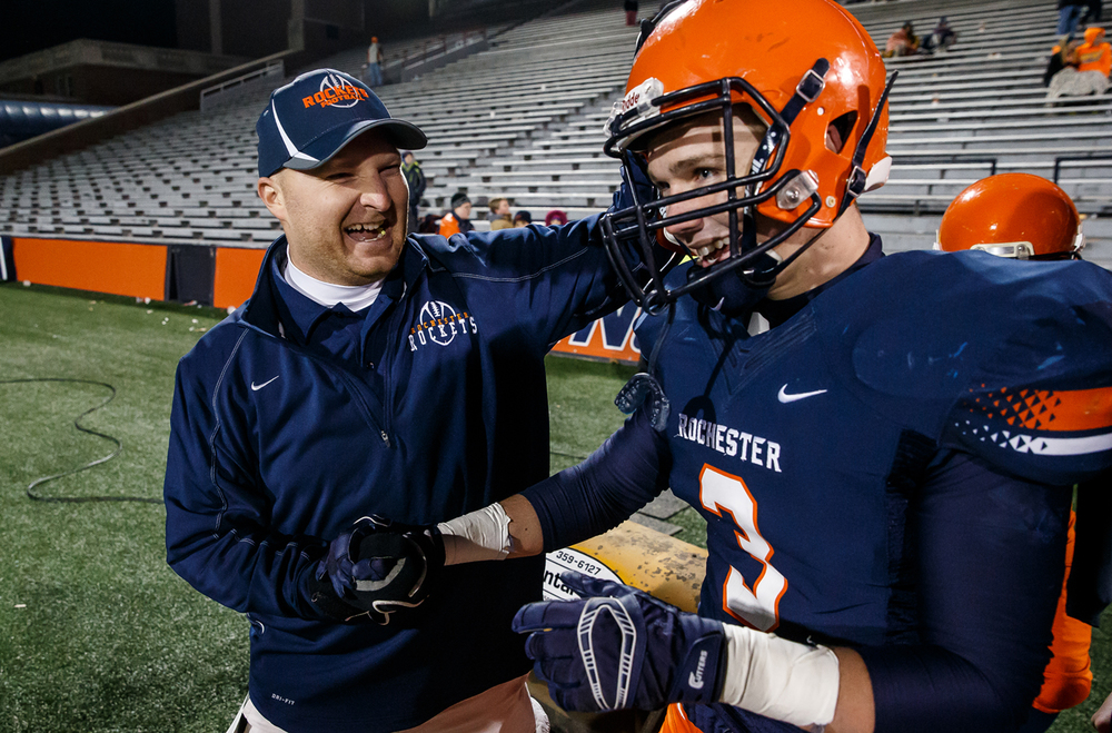 Rochester defensive coordinator Steve Buecker celebrates with Rochester's Christian Lett (3) as the Rockets claim their fifth title against Chicago Phillips in the IHSA Class 4A state championship game at Memorial Stadium, Friday, Nov. 28, 2014, in Champaign, Ill. Justin L. Fowler/The State Journal-Register