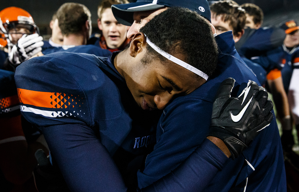 Rochester's Nathaniel Johnson (17) hugs Rochester defensive coordinator Steve Buecker after the Rockets won their fifth straight title against Chicago Phillips in the IHSA Class 4A state championship game at Memorial Stadium, Friday, Nov. 28, 2014, in Champaign, Ill. Justin L. Fowler/The State Journal-Register