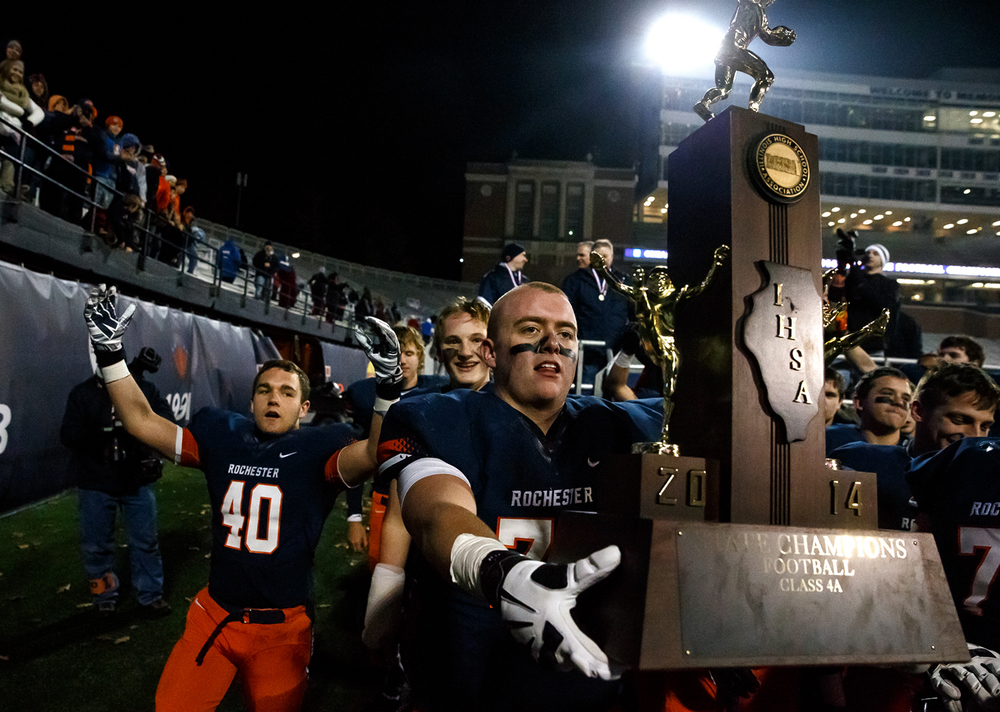 Rochester's Zach Wenger (74) shares the Rockets fifth straight title with the fans after they defeated Chicago Phillips in the IHSA Class 4A state championship game at Memorial Stadium, Friday, Nov. 28, 2014, in Champaign, Ill. Justin L. Fowler/The State Journal-Register