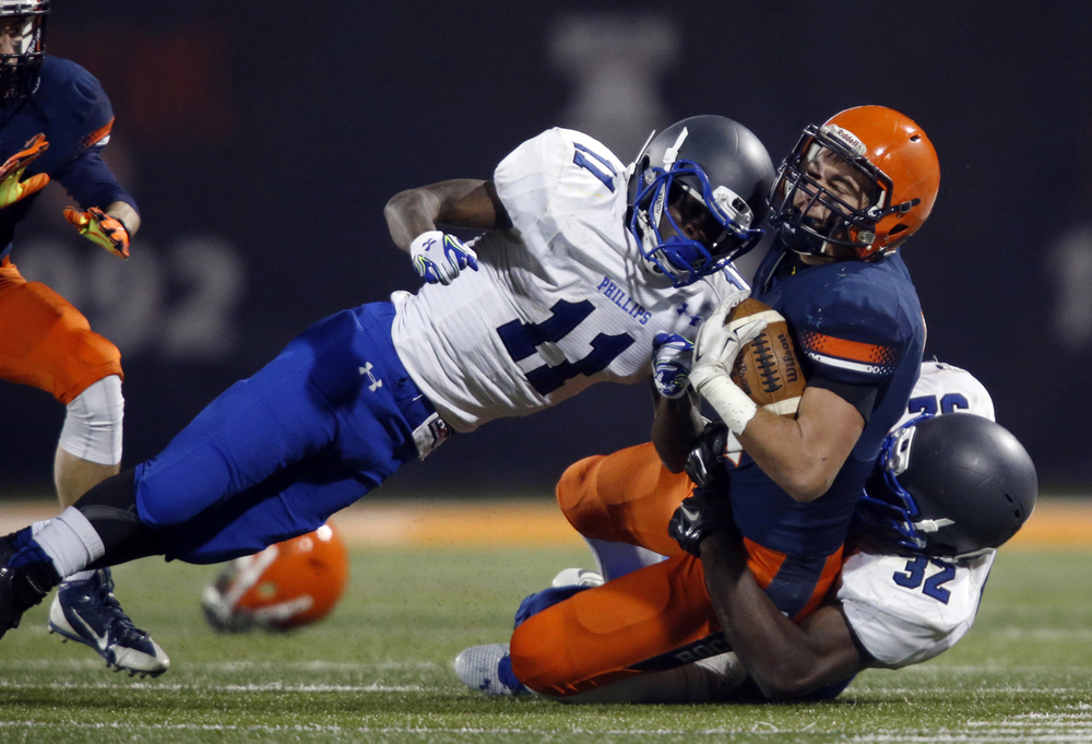Chicago Phillips' Corey Warren crashes into Rochester's Evan Sembell during the Class 4A football championship game at Memorial Stadium Friday, Nov. 28, 2014. Ted Schurter/The State Journal-Register