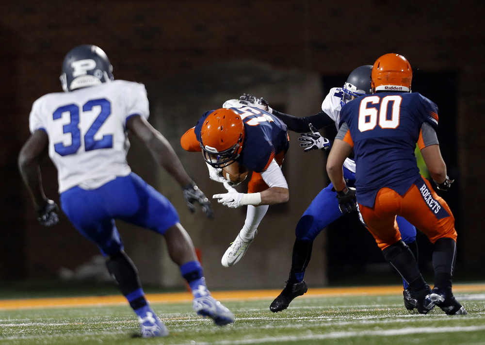 Rochester's  Jeremy Bivens gets hit after making a catch against Chicago Phillips during the Class 4A football championship game at Memorial Stadium Friday, Nov. 28, 2014. Ted Schurter/The State Journal-Register