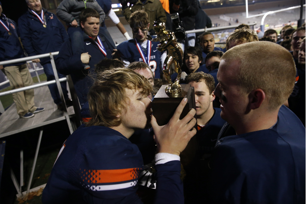 Rochester's quarterback Danny Zeigler kisses the trohpy as the Rockets celebrate their victory against Chicago Phillips during the Class 4A football championship game at Memorial Stadium Friday, Nov. 28, 2014. Ted Schurter/The State Journal-Register