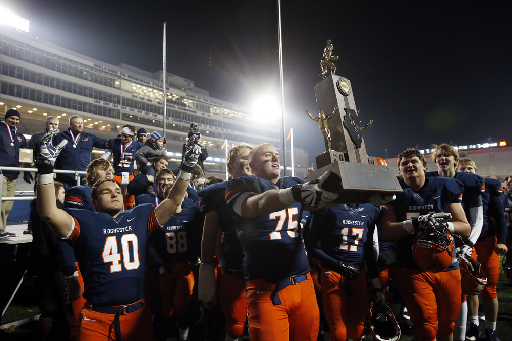 Rochester's Connor Brewer and the Rockets present the championship trophy to the fans in the stands after beating Chicago Phillips during the Class 4A football championship game at Memorial Stadium Friday, Nov. 28, 2014. Ted Schurter/The State Journal-Register
