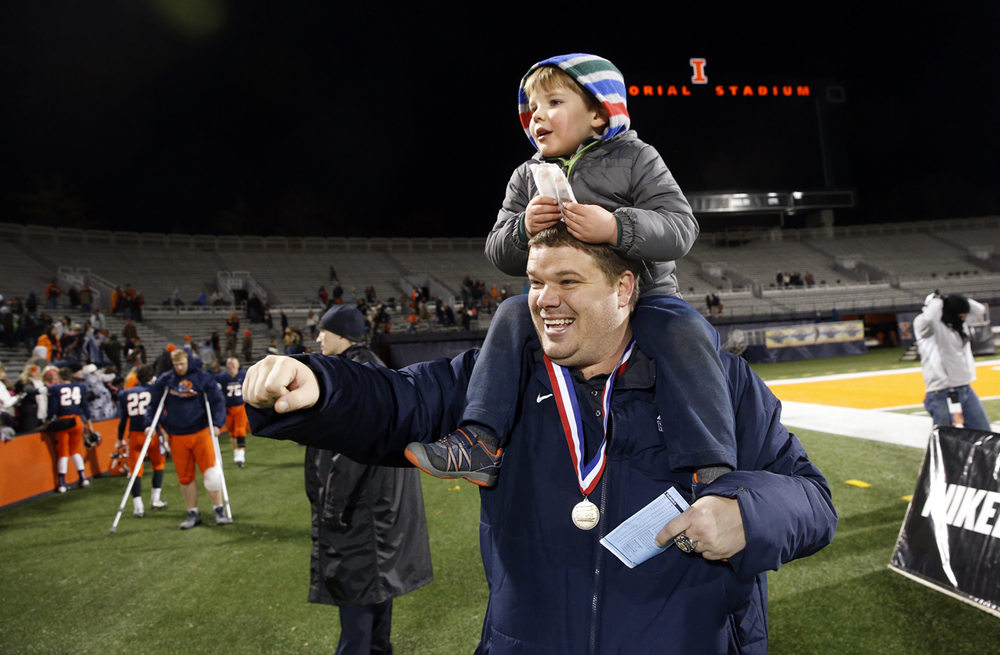 Rochester head coach Derek Leonard and his son Blake wave to the fans after the Rockets beat Chicago Phillips during the Class 4A football championship game at Memorial Stadium Friday, Nov. 28, 2014. Ted Schurter/The State Journal-Register