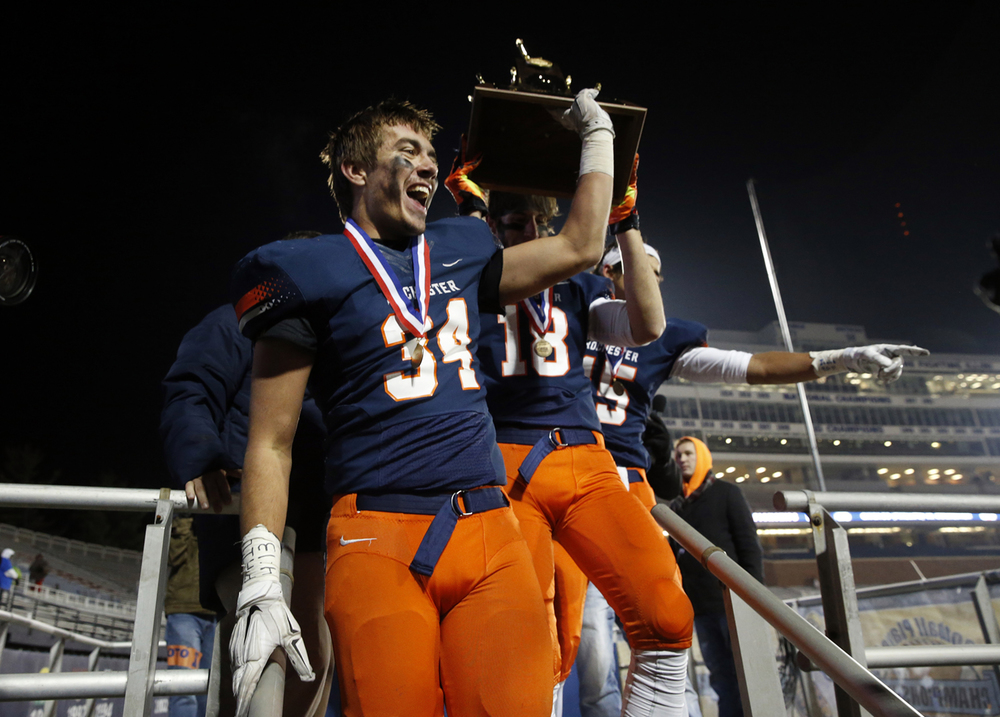 Rochester's Evan Sembell and the Rockets bring the championship trophy down the stage after defeating Chicago Phillips during the Class 4A football championship game at Memorial Stadium Friday, Nov. 28, 2014. Ted Schurter/The State Journal-Register