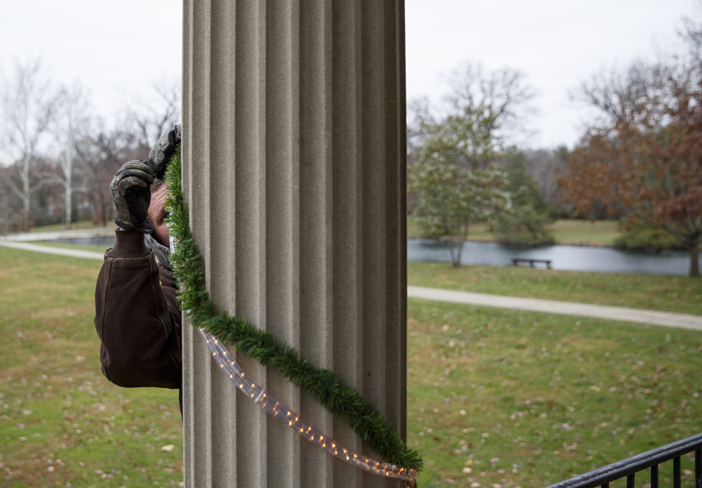 Matthew Evans ties off a string of lights and garland on the Louis Lehmann band shell in Washington Park Monday, Nov. 24, 2014. Evans, part of a crew from the Springfield Park District, decorated the columns of the 88-year-old structure and put lights in the bushes around the base for the holiday season. Rich Saal/The State Journal-Register