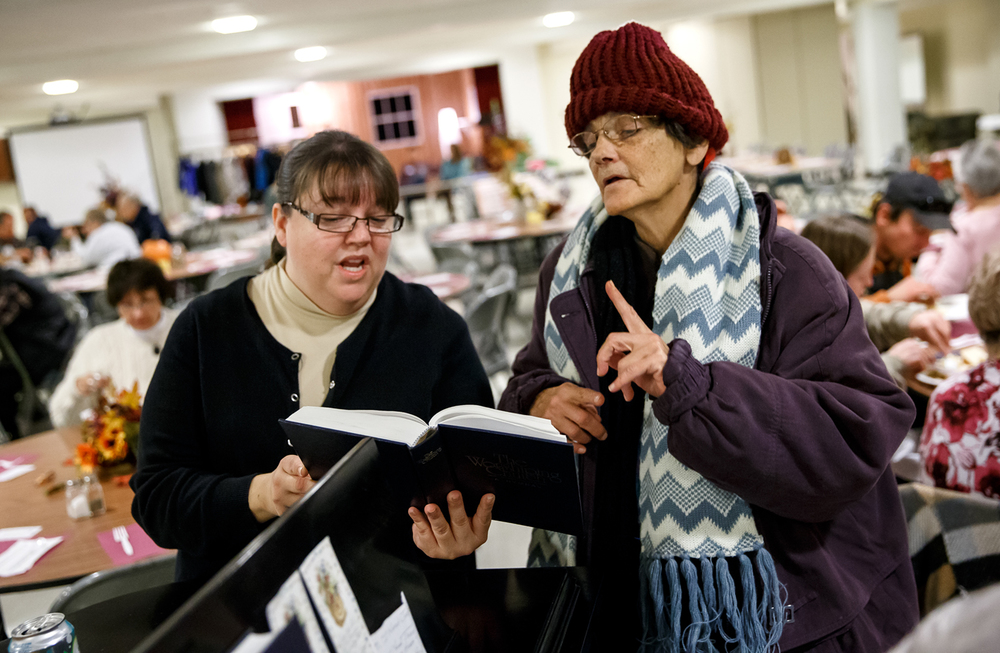 Jennie Alt ,left, a volunteer and member of the church, Sue Houston, right, sing a hymnal together during the Central Baptist Church's 29th Feast of Plenty free Thanksgiving meal to the public at the church, Thursday, Nov. 27, 2014, in Springfield, Ill. Justin L. Fowler/The State Journal-Register