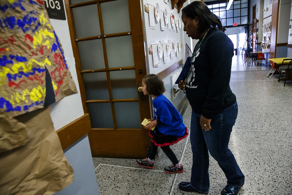 Ava Moore, 5, serving as principle for the day, peaks into a class room as she prepares to go in to hand out compliment cards with Principal Tracy Gage at Butler Elementary School, Wednesday, Nov. 26, 2014, in Springfield, Ill. Justin L. Fowler/The State Journal-Register