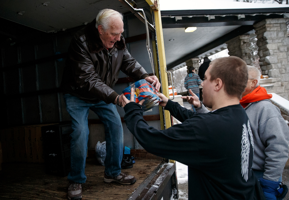 "Volunteer Clyde Bunch, left,  takes a donation of canned goods from Sacred Heart-Griffin junior George Jennings, right, to benefit St. Martin de Porres during Sports Radio 1450's AM Springfield 19th Annual Thanksgiving Walk in Lincoln Park, Thursday, Nov. 27, 2014, in Springfield, Ill. ""It's a day for giving and helping those in need, thats why we do this,"" said Bunch. Justin L. Fowler/The State Journal-Register"