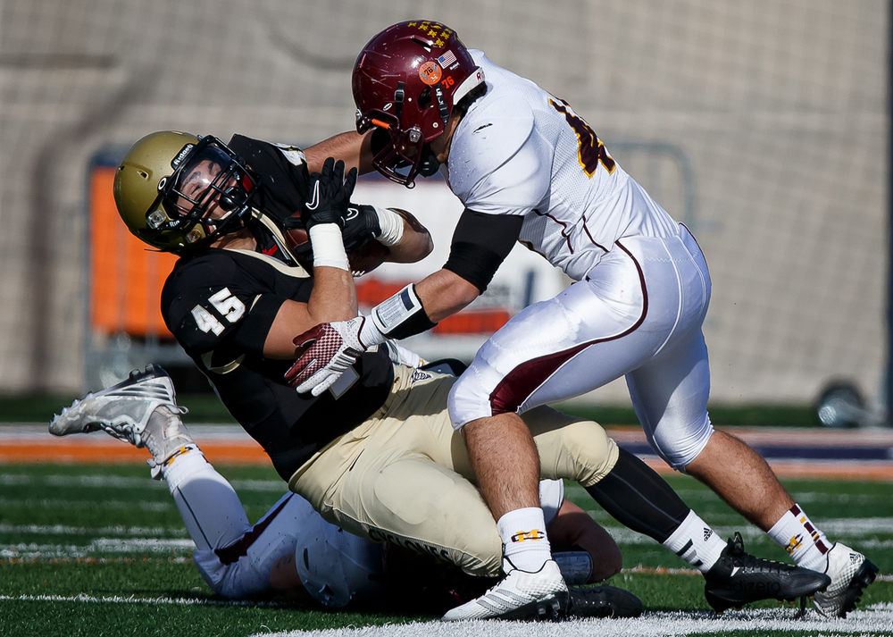 Sacred Heart-Griffin's Anthony DiNello (45) takes a hard hit from Lombard Montini's Samuel Asta (48) on a rush in the first half during the IHSA Class 5A state championship game at Memorial Stadium, Saturday, Nov. 29, 2014, in Champaign, Ill. Justin L. Fowler/The State Journal-Register
