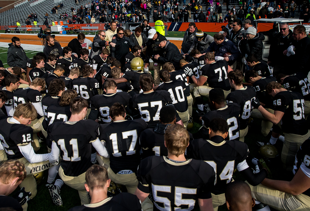 The Cyclones hold a prayer with Bishop Thomas John Paprocki after they defeated Lombard Montini 29-14 in the IHSA Class 5A state championship game at Memorial Stadium, Saturday, Nov. 29, 2014, in Champaign, Ill. Justin L. Fowler/The State Journal-Register