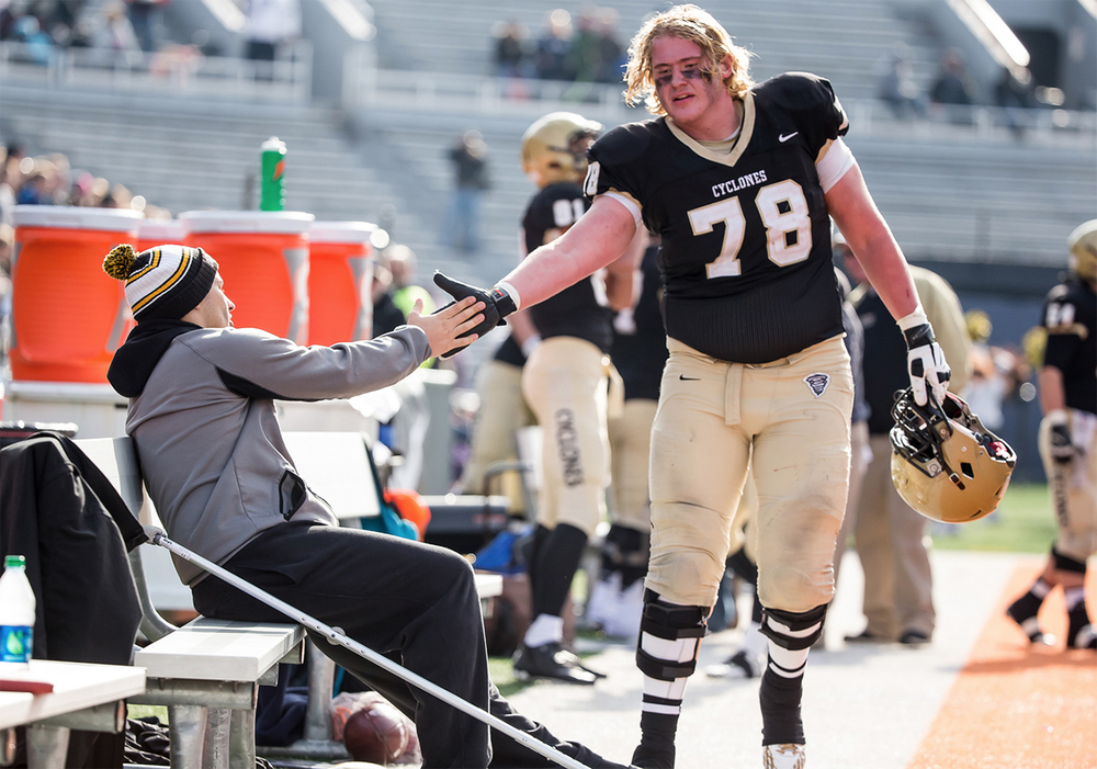 Sacred Heart-Griffin's Quinn Oseland (78) gets a hand shake from an injured Anthony DiNello (45) on the sidelines as the Cyclones take on Lombard Montini in the second half during the IHSA Class 5A state championship game at Memorial Stadium, Saturday, Nov. 29, 2014, in Champaign, Ill. Justin L. Fowler/The State Journal-Register
