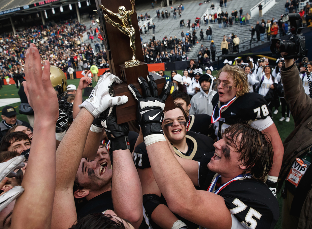 Sacred Heart-Griffin's Michael Zeigler (75) and his teammates celebrate with the championship trophy after defeating Lombard Montini 29-14 in the IHSA Class 5A state championship game at Memorial Stadium, Saturday, Nov. 29, 2014, in Champaign, Ill. Justin L. Fowler/The State Journal-Register