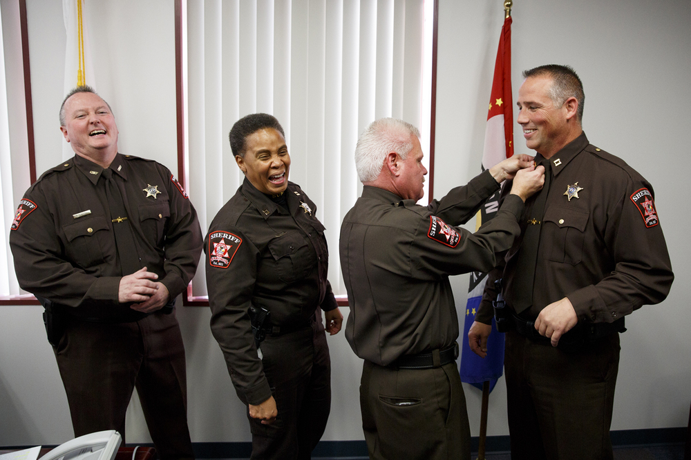 Sangamon County Sheriff Wes Barr draws a laugh from his command staff when he straightens the captain bars for Gerald Felts, who he had just promoted to captain in charge of the detective bureau during a ceremony in his office Monday, Dec. 1, 2014. Barr also promoted Joe Roesch, left, to chief deputy. Capt. Cheryllyn Williams will remain in her role as captain in charge of the operations division. Barr was sworn in as sheriff earlier in the day. Rich Saal/The State Journal-Register