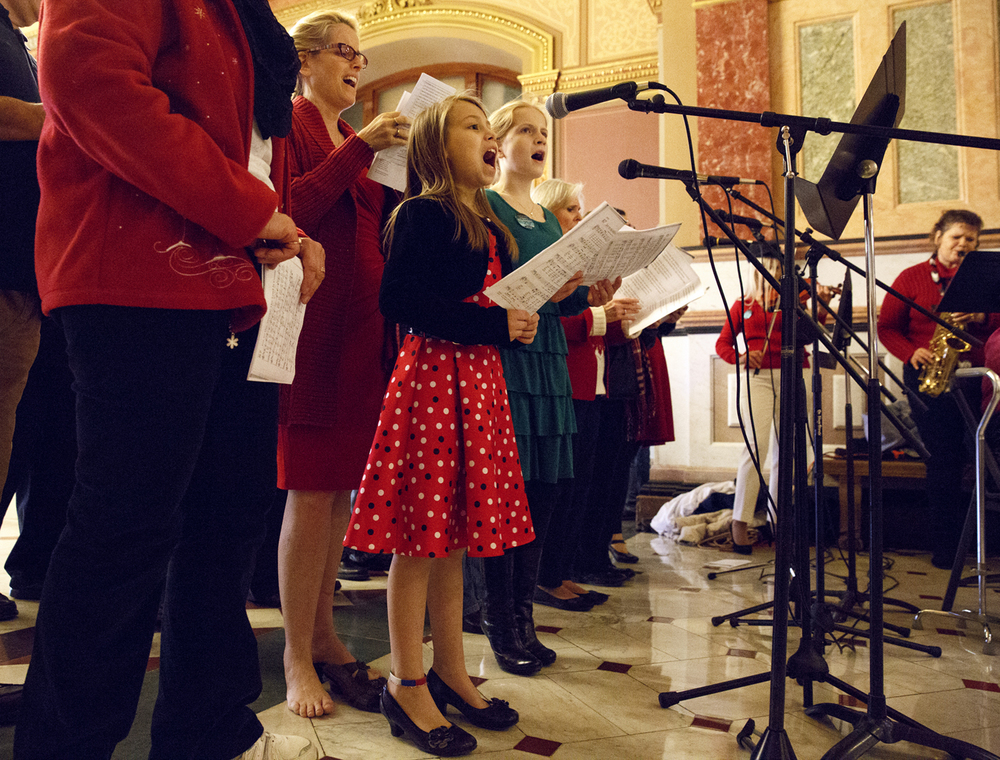 Kristen Housam adds her voice to Christmas carols sung by members of the First Baptist Church Praise Team during the dedication of the Nativity scene at the Illinois State Capitol Tuesday, Dec. 2, 2014. Sponsored by the Springfield Nativity Scene Commitee and underwritten by the Thomas More Society of Chicago, it's the 7th year the display has been placed in the rotunda. Rich Saal/The State Journal-Register