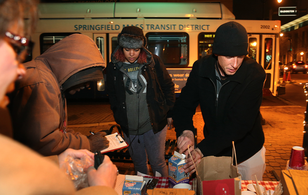Springfield resident Gabriel Slinkard, right, helps himself to free coffee after he and others signed petitions Thursday night advocating for increased night and weekend bus service. Marking seven years of evening bus service, volunteers with the Springfield Transportation Advocacy Group (STAG) distributed free coffee to those riding SMTD busses at the night transfer center in downtown Springfield  Thursday, Dec. 4, 2014. The group is starting a lobbying effort to gather signatures in support of bus service on Saturday evenings and Sundays. David Spencer/The State Journal-Register