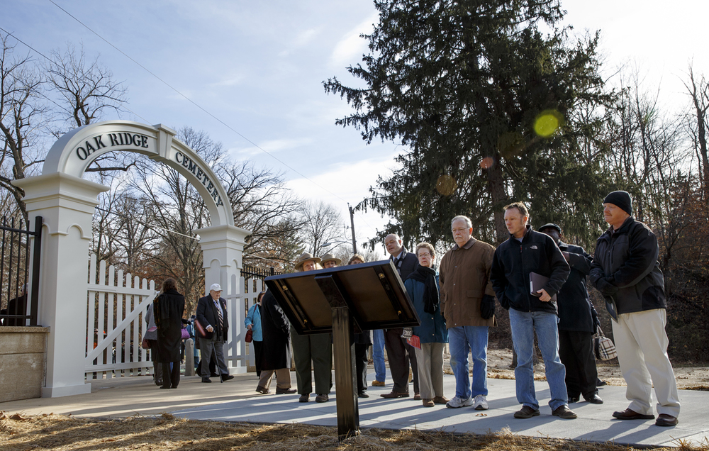 Guests pause to read a plaque about the history of the original entrance to Oak Ridge Cemetery after a dedication ceremony for the newly constructed entrance Wednesday, Dec. 3, 2014. Ted Schurter/The State Journal-Register