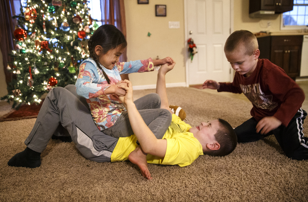 Ava wrestles with her brothers Noah and Luke in the Lyons Waverly home Thursday, Dec. 4, 2014. Ted Schurter/The State Journal-Register
