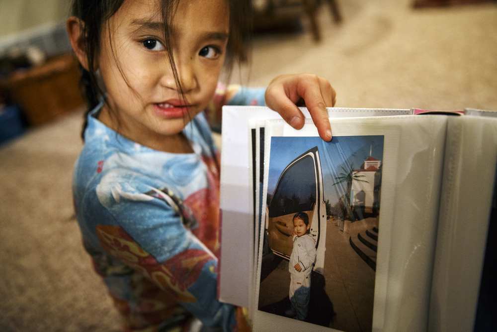 Ava Lyons shows a photo of herself leaving the Chinese orphanage where she lived before meeting her adoptive parents on May 2, 2012. Ted Schurter/The State Journal-Register