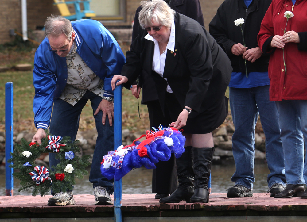 Memorial wreaths are tossed into Lake Springfield by Sons and Daughters of Pearl Harbor Survivors Illinois president Steve Browning at left and Gwen Diehl of the Illinois Department of Veterans' Affairs, who was master of ceremonies at the event. A dual ceremony honoring the 73rd anniversary of the attack on American naval forces at Pearl Harbor and the 10th anniversary of the dedication of the World War II memorial in Springfield took place at the Disabled American Veterans Hall at Lake Springfield on Sunday, Dec. 7, 2014. David Spencer/The State Journal-Register