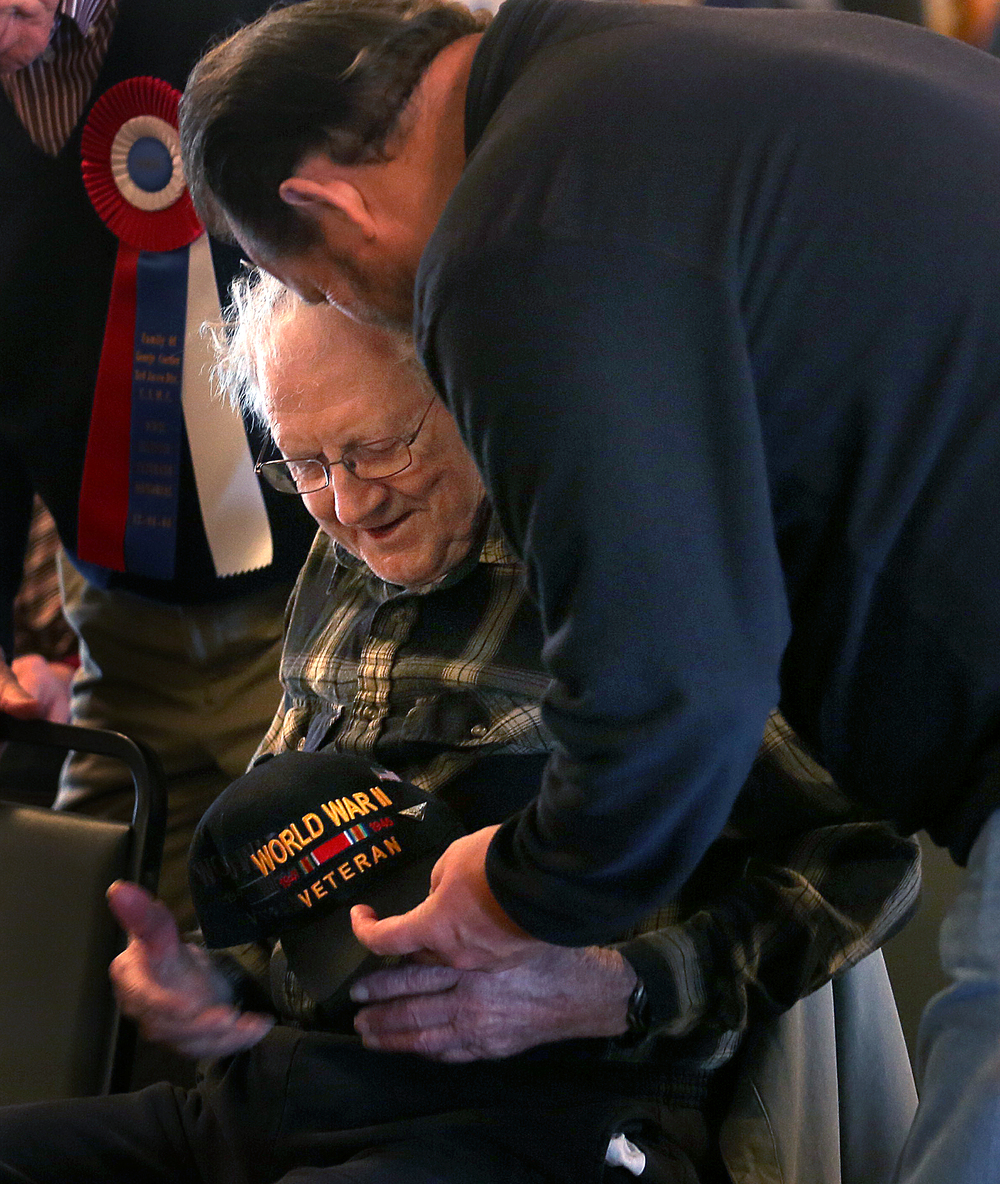 Larry Edwards, 94 of Rochester, one of three WWII veterans in attendance at Sunday's ceremony and the charter president of the Oak Ridge Cemetery World War II monument memorial committee is helped with his veterans ballcap by nephew Bryan Edwards of Vandalia on Sunday. A dual ceremony honoring the 73rd anniversary of the attack on American naval forces at Pearl Harbor and the 10th anniversary of the dedication of the World War II memorial in Springfield took place at the Disabled American Veterans Hall at Lake Springfield on Sunday, Dec. 7, 2014. David Spencer/The State Journal-Register