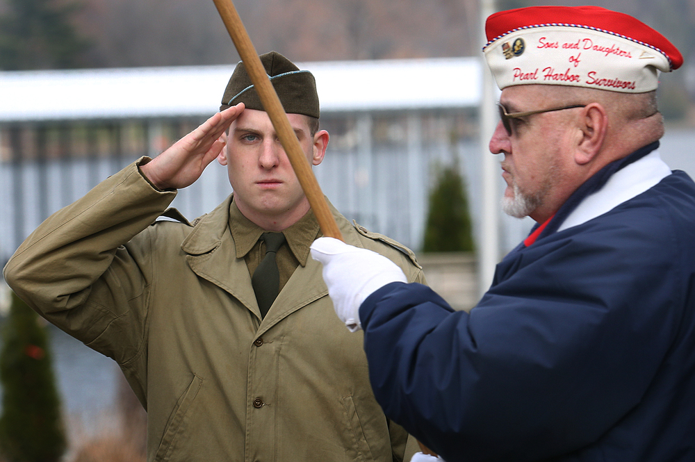 Matt LeMasters, wearing WWII civilian clothing and a reenactor with the Illinois State Military Museum salutes while flag bearer Lynn Shindel, Illinois state chairman of the Sons and Daughters of Pearl Harbor Survivors passes by after the wreath laying ceremony at Lake Springfield at the DAV Sunday morning. A dual ceremony honoring the 73rd anniversary of the attack on American naval forces at Pearl Harbor and the 10th anniversary of the dedication of the World War II memorial in Springfield took place at the Disabled American Veterans Hall at Lake Springfield on Sunday, Dec. 7, 2014. David Spencer/The State Journal-Register