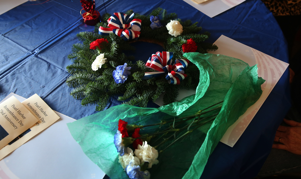 An evergreen wreath and carnations that would be tossed into Lake Springfield as a memorial to those who perished as a result of the surprise attack on Pearl Harbor in 1941 lays on a table inside the hall Sunday morning. A dual ceremony honoring the 73rd anniversary of the attack on American naval forces at Pearl Harbor and the 10th anniversary of the dedication of the World War II memorial in Springfield took place at the Disabled American Veterans Hall at Lake Springfield on Sunday, Dec. 7, 2014. David Spencer/The State Journal-Register